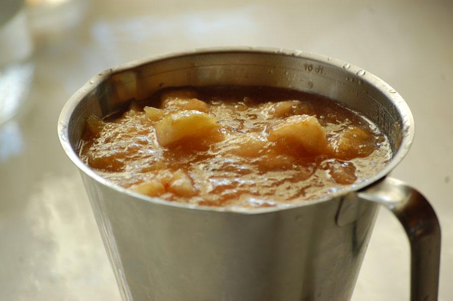 Äppelmos upphällt i literkannan för att lättare få ner den i burkar
